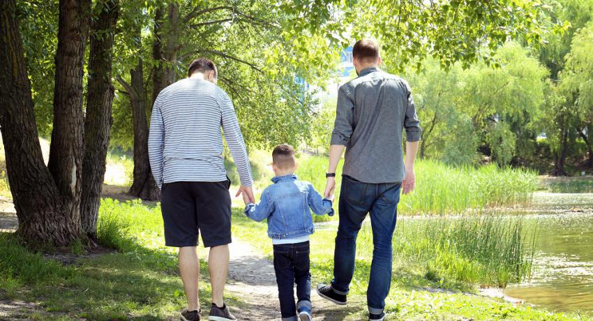 Same-sex parents walking hand in hand with their child in a park.